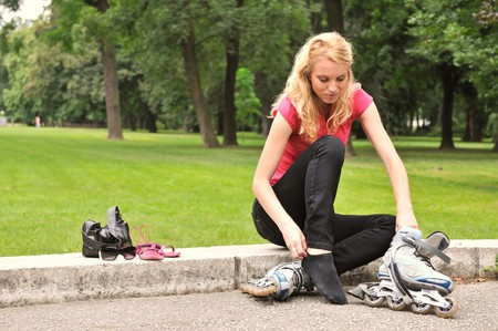 roller blade: Young woman taking on roller skates - outdoors in park