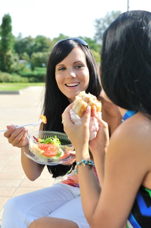 Two friends - smiling young women eating together outdoors on sunny day photo