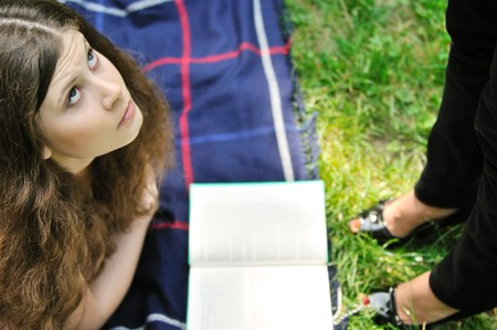 annoy: Young woman stydying in park on rug is disturbed by another person (torso visible only) Stock Photo