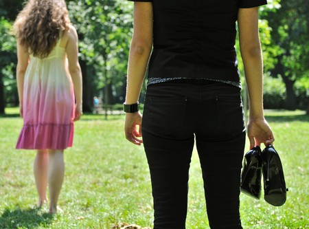 One woman stands turned back to her friend who holds shoes in hand Stock Photo - 7807674
