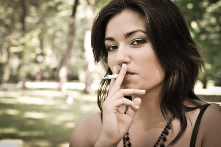women smoking: Portrait of young woman smoking cigarette outdoors in sunny green park Stock Photo