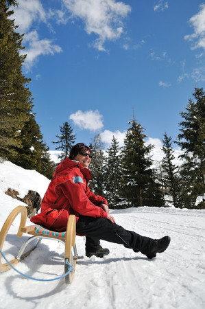 sunning: Senior woman siting on sledge sunning in mountain winter snow landscape with blue sky