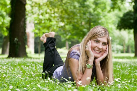 crossed legs: Young smiling woman lying in grass during sunny day (park - outdoors)