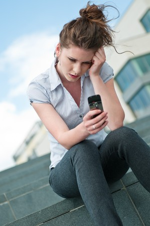 woman typing: Young unhappy woman typing on mobile phone - outdoors in street Stock Photo