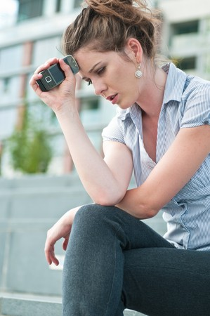 femme inqui�te: Jeune femme inqui�te � l'expression malheureuse tenant t�l�phone mobile - � l'ext�rieur en milieu urbain