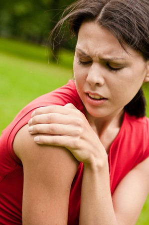 face and shoulders: Shoulder injury - sportswoman in pain