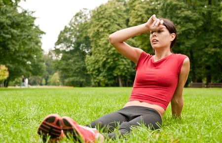 agotado: Relajarse en la hierba - mujer cansada después de deporte