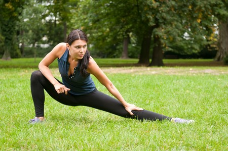 Woman performs stretching before sport in park photo