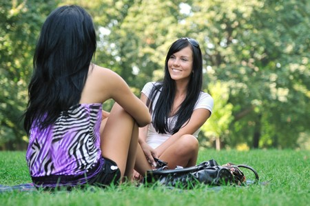 Youth lifestyle park scene - two young friends (girls) talking outdoors. Siting on rug laid in grass. Stock Photo - 7807711