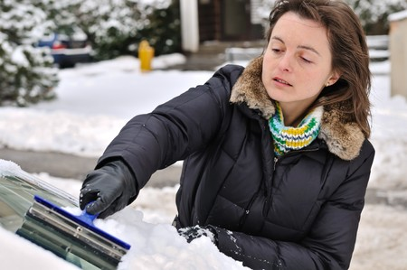 clean street: Young woman cleaning car windows from snow in winter season Stock Photo