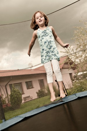 Small cute child jumping on trampoline - garden and family house in background (sepia tone) photo