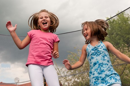 Small cute children jumping on trampoline - garden and family house in background photo