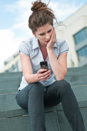 Young unhappy woman typing on mobile phone - outdoors in street Stock Photo - 7955072