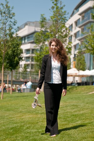 Young business woman walking barefoot outdoors in grass next to her office photo