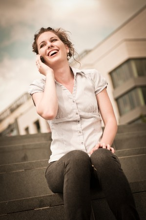 Young beautiful laughing woman calling with mobile phone - old fashioned look photo