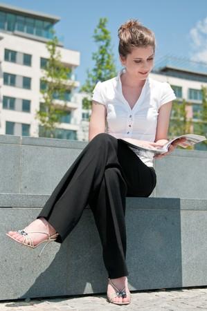 brak: Young business woman sitting outdoors reads magazine Stock Photo