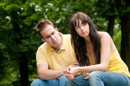 Young couple sitting outdoors on bench having relationship problems photo