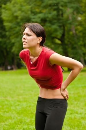 Backpain - sportswoman in pain Stock Photo