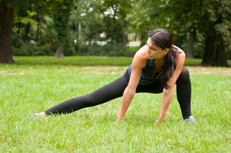 Woman performs stretching before sport in park Stock Photo - 7955078