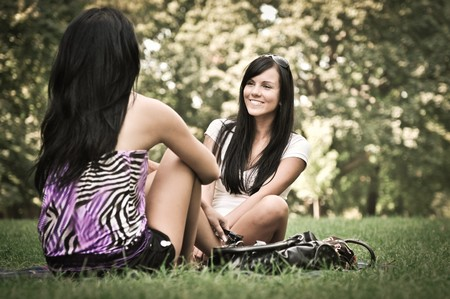 Youth lifestyle park scene - two young friends (girls) talking outdoors. Siting on rug laid in grass. Stock Photo - 7955066