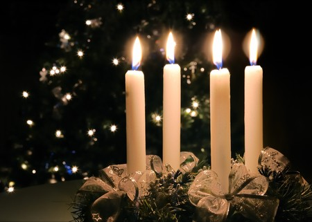 advent candles: Christmas advent wreath with burning candles. Lights on x-mas tree in background