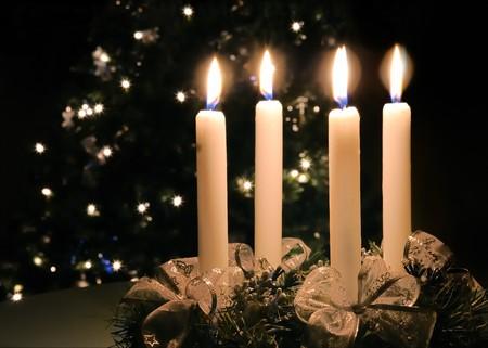 �advent: Corona de llegada de Navidad con la grabaci�n de velas. Luces del �rbol de x-mas en el fondo de