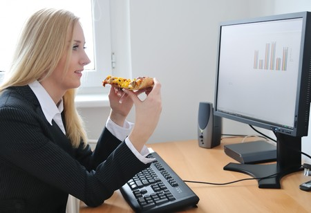 Young business woman looking on monitor and eating pizza photo