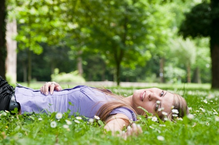 arms above head: Detail of young woman lying in fresh green grass with flowers - low angle view