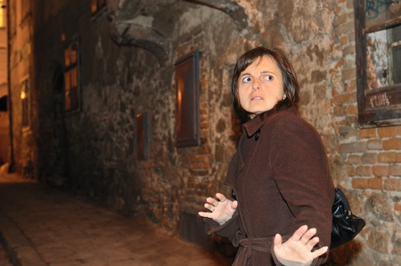 Fear from assault - young woman alone on street in the night awaiting someone from behind                             photo