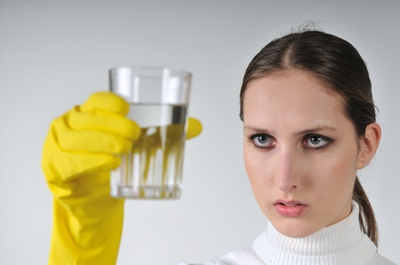 hygienic: Young woman in yellow hygienic gloves holding glass of water - concentration                             Stock Photo