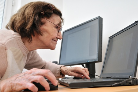 senior computer: 80-something senior woman working with laptop, another computer in the background