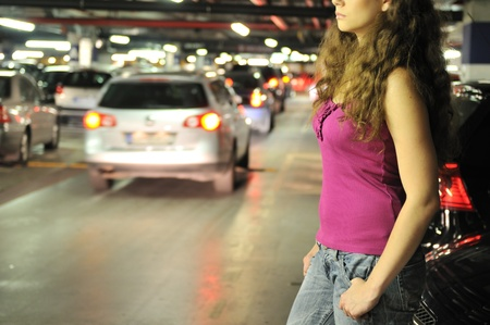 Young woman standing at car in underground parking place                        photo