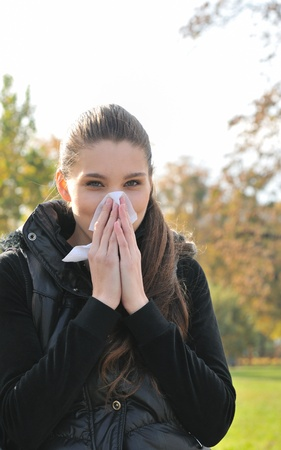Young woman with cold wiping nose - winter outdoors lifestyle scene                       photo