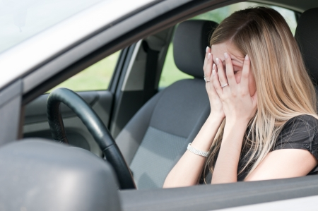 Young woman with hands on eyes sitting depressed in car photo