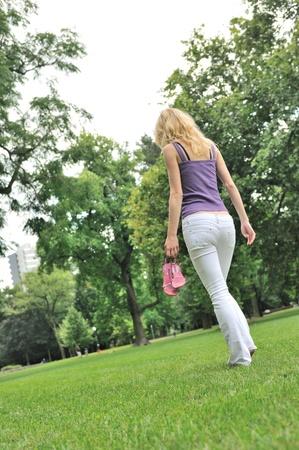 piedi nudi di bambine: Donna Yyoung tenendo le scarpe e camminare a piedi nudi sull'erba nel parco - vista posteriore