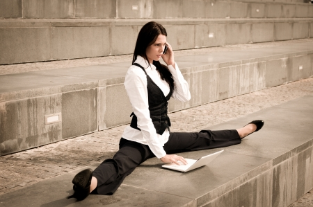 Young business woman in gymnastics pose working with computer and calling mobile phone