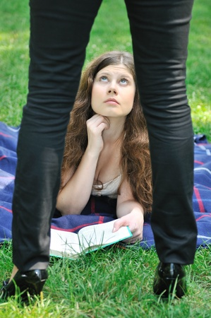 One woman (legs visible only) disturbing another young woman reading book photo