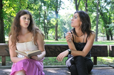 women smoking: Two young people outdoors on bench in park, one teenager smoking cigarette annoys another girl