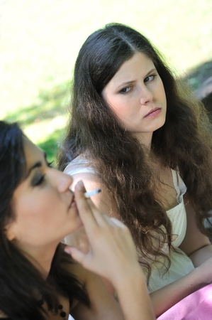 scowl: Youth culture - two young people outdoors, one woman smoking cigarette annoys and iritates another girl Stock Photo