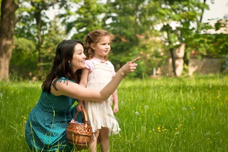 Mother shows with finger to her cute little daughter something interesting in distance Stock Photo