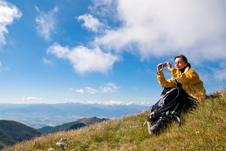 Young person relaxes on hiking in mountains and taking photo with mobile phone Stock Photo