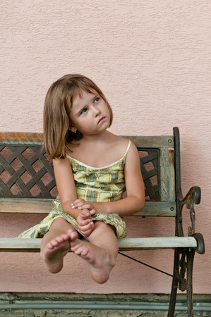 Portrait of cute child sitting on bench and stretching barefoot legs photo