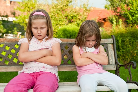 angry child: Small girls (sisters) siting on bench offended after quarrel - outdoors in backyard
