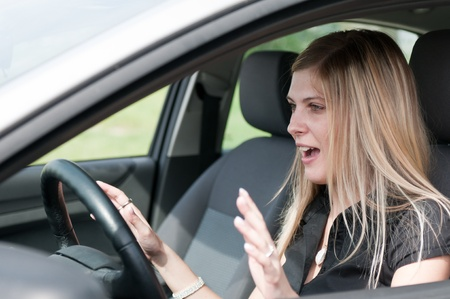 Young woman with fear in eyes driving car - hands not on steering wheel photo