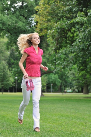 Smiling young woman running barefoot on grass in park and holding her shoes in hand                            photo