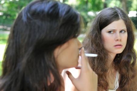 joven fumando: Cultura juvenil - dos j�venes al aire libre, una mujer fumar cigarrillos molesta y iritates otra chica