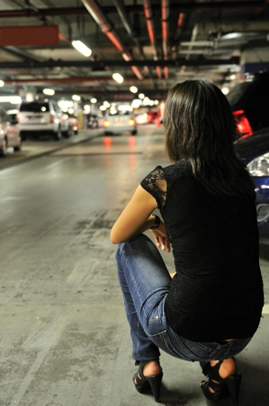 crouching: Young woman crouching and waiting in underground parking place - cars in background