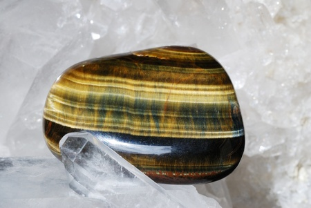 esoterics: Tiger eye gem energized on druze of quartz crystals. This gem is used as a jewel stone and also in alternative medicine and esoterics (connected with 3rd chakra).