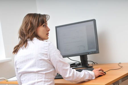 head and shoulders: Business person works at table with computer and looks over shoulder who is coming                   Stock Photo
