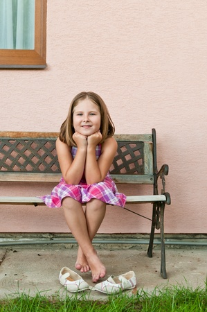 girls feet: Portrait of cute smiling child sitting on bench - wall in background Stock Photo